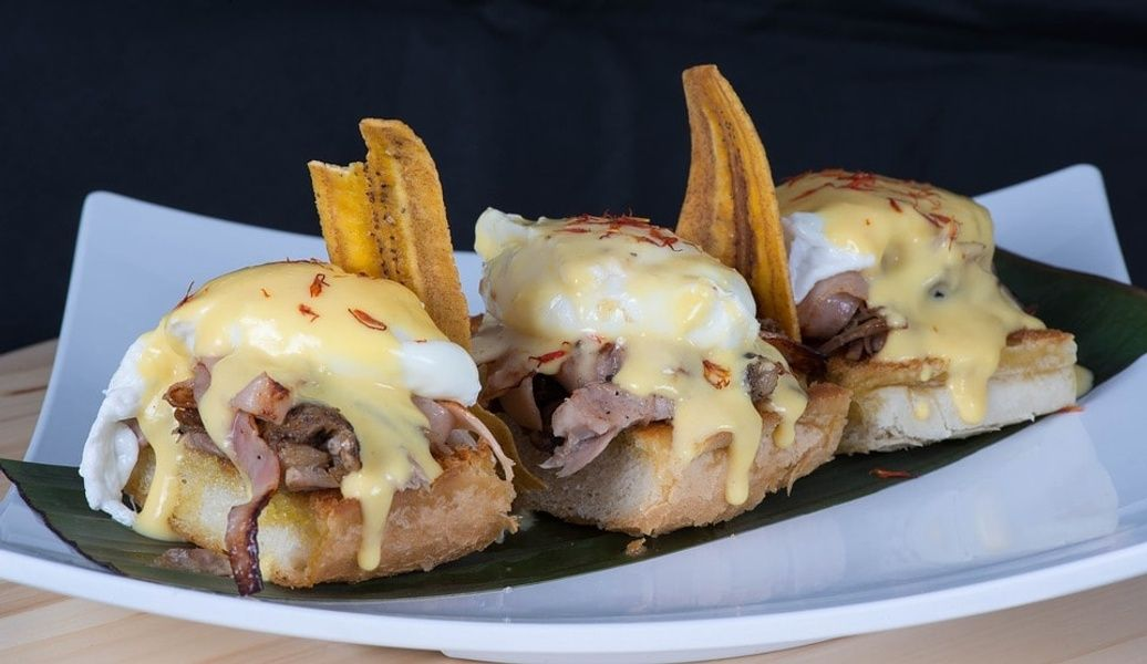 Breakfast sandwiches on a white plate with ham eggs and cheese cheap food in Cuba