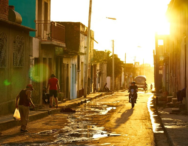 People motorcycling and walking in an alley things to do in Trinidad Cuba