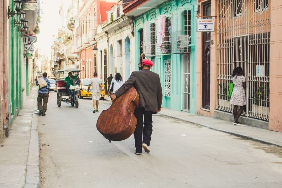 Man walking in Cuba with cello