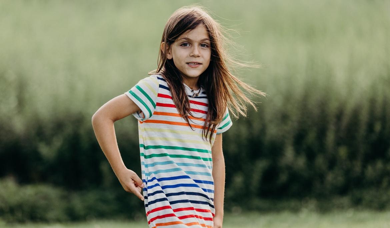 little boy with long hair wears primary kids rainbow stripe t shirt dress