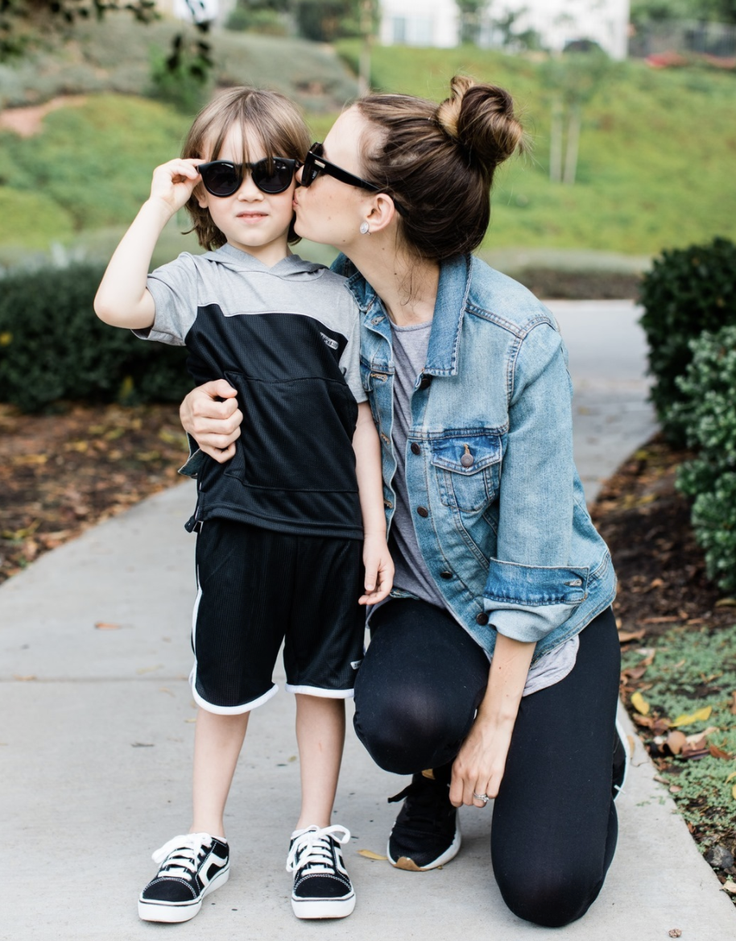 Boy in kidpik clothes being kissed by mom