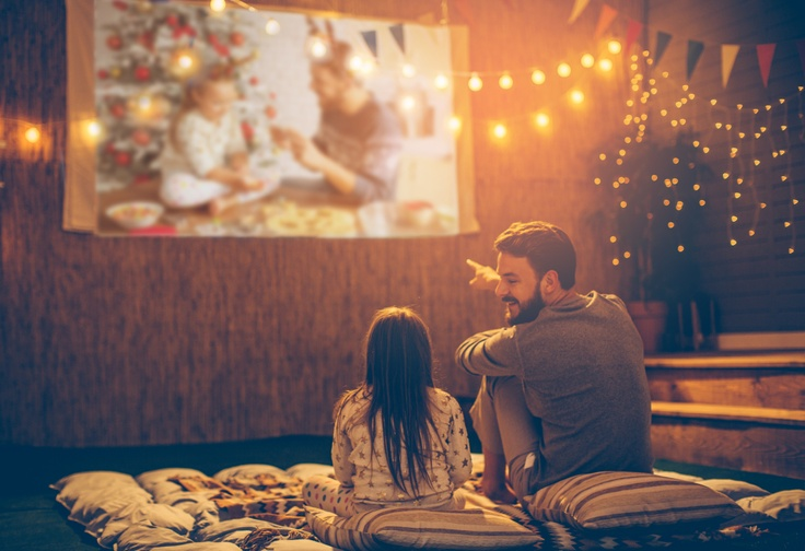 kid and dad having an outdoor movie night