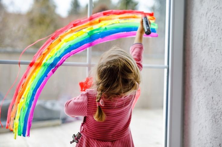 Girl painting rainbow on window