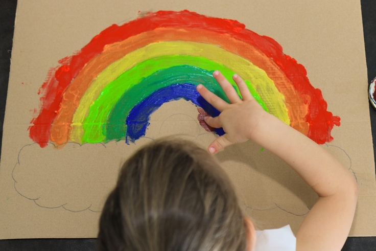 Girl painting rainbow with fingerpaints
