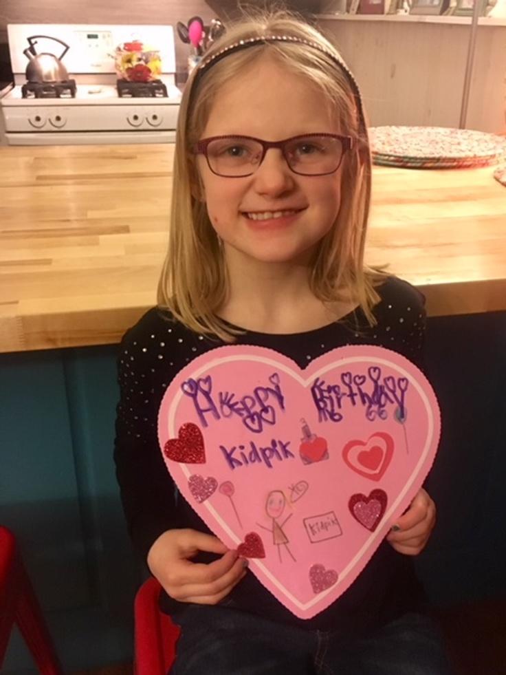 Girl holding happy birthday kidpik card