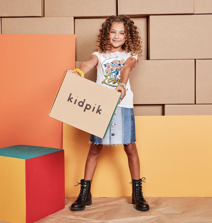Girl holding kidpik fashion subscription box