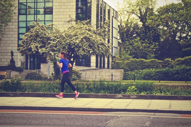 A runner makes her way down a sidewalk.