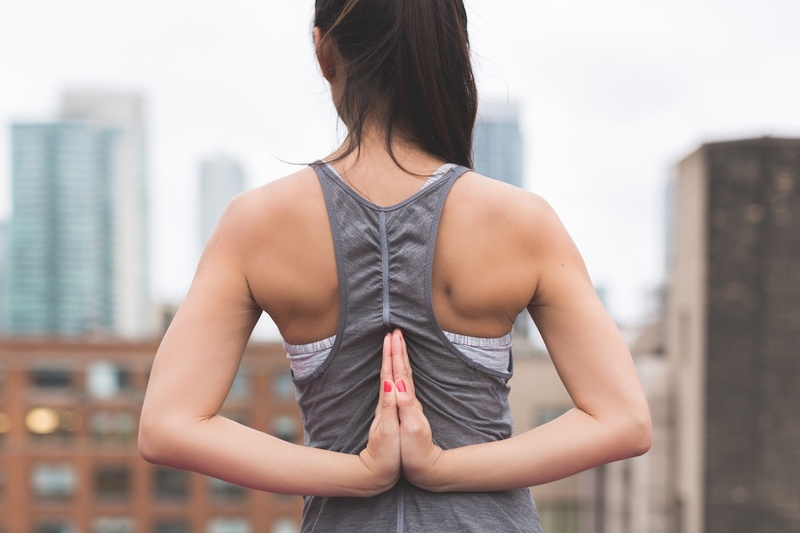 A woman practices yoga on a rooftop.